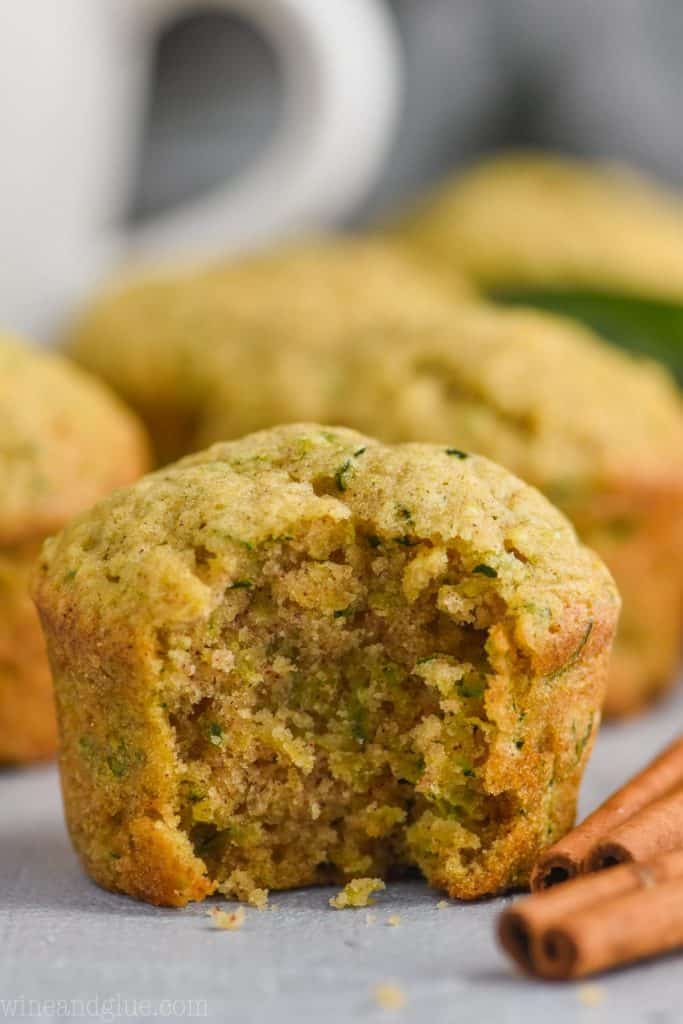 close up picture of a zucchini muffin with a bite out of it and two cinnamon sticks on the side.