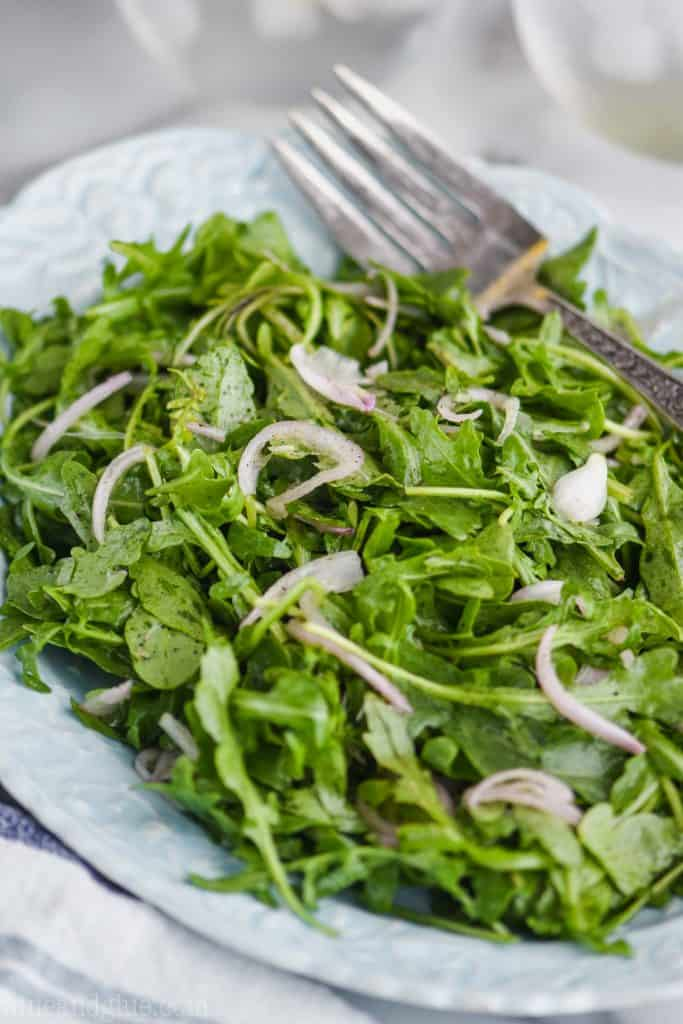 close up view of an easy arugula salad recipe with thin slices of shallot on a teal plate