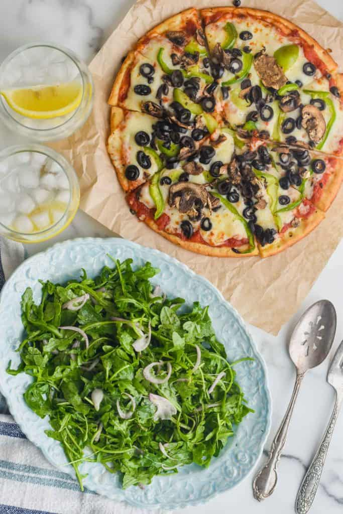 overhead view of arugula salad on an oval plate next to a 10 inch cauliflower crusted pizza topped with peppers, mushrooms, and olives