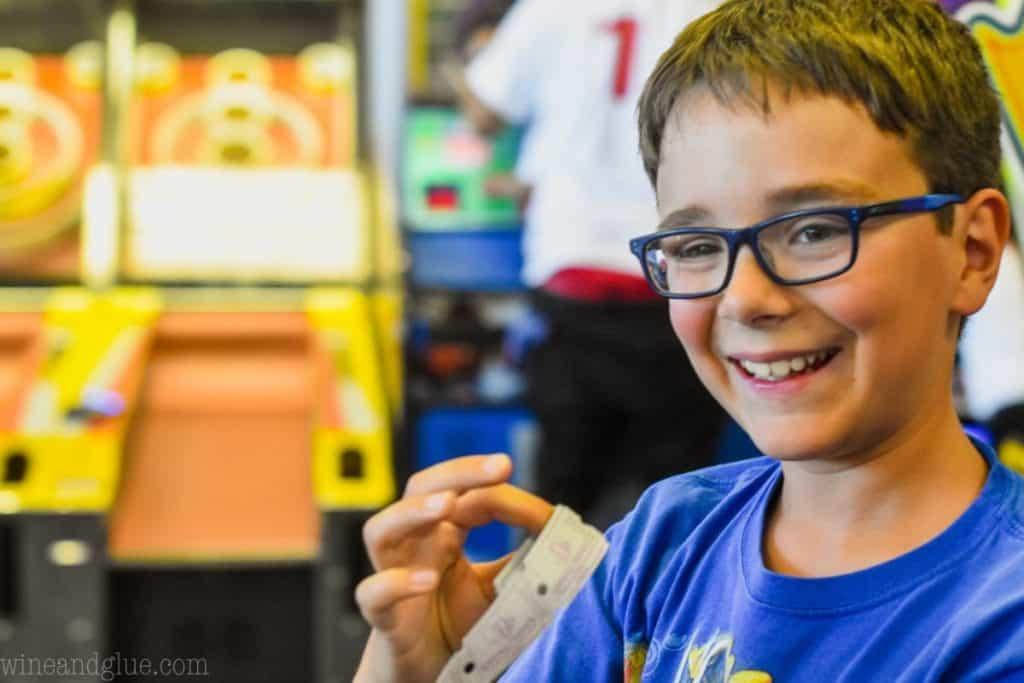 boy holding chuck e cheese tickets