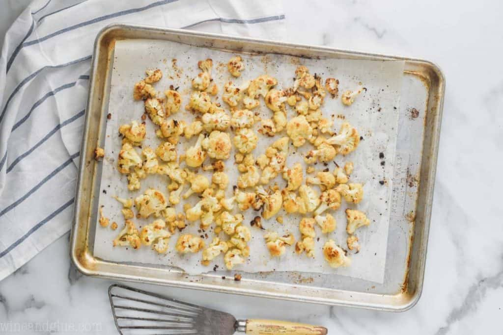 overhead view of roasted cauliflower recipe on a baking sheet that is lined with parchment paper, on a marble countertop with a striped kitchen towel underneath the baking sheet