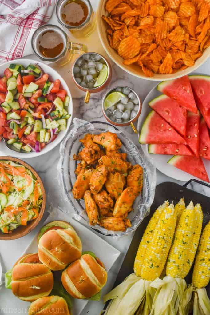 overhead view of a table filled with food for a party: crock pot chicken wings in the middle, corn that was grilled, fresh watermelon, potato chips, salads, and hamburgers