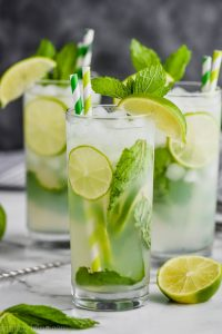 three high ball glasses on a white surface against a gray background filled with lime slices, a mojito recipe, fresh mint leaves, and garnished with green and white stripped straws, fresh mint and a lime wedge