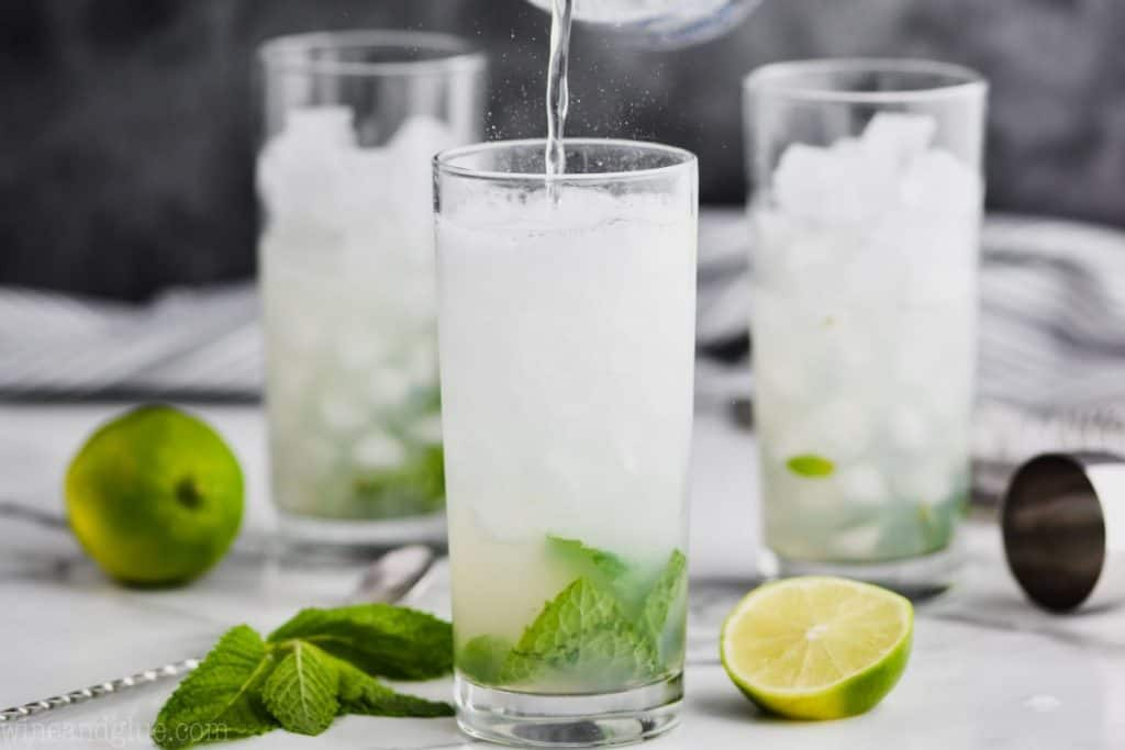 three glasses filled with ice, with mint and lime infront of the first glass and club soda being poured into it to make a mojito cocktail