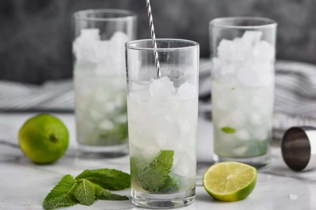 three glasses filled with ice with the first one being mixed by a long spoon to make a mojito