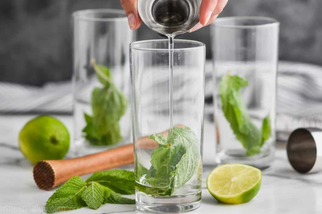 three high ball glasses with mint leaves in them and simple syrup is being poured into the first glass