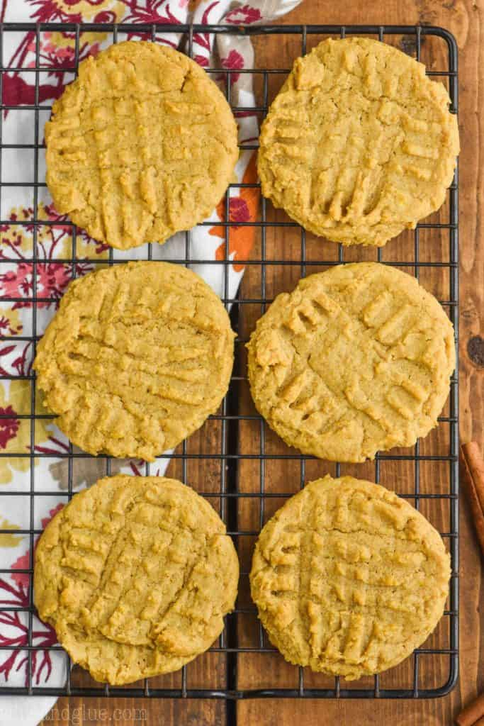 six pumpkin peanut butter cookies on a cool rack (overhead view), a fall themed cloth napkin underneath on a wood board