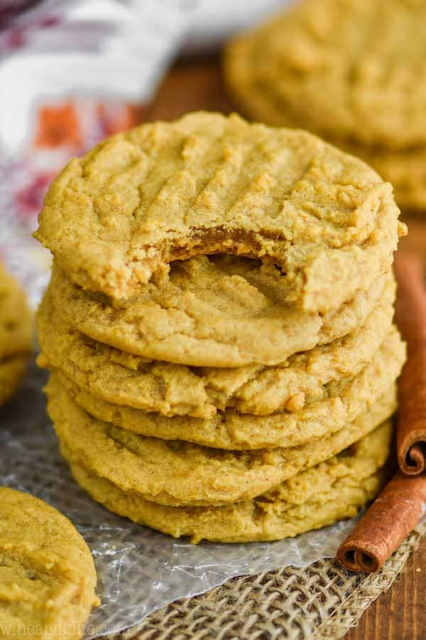 stack of pumpkin peanut butter cookies on wax paper on burlap with a cinnamon stick next to them and a bite out of the top cookie