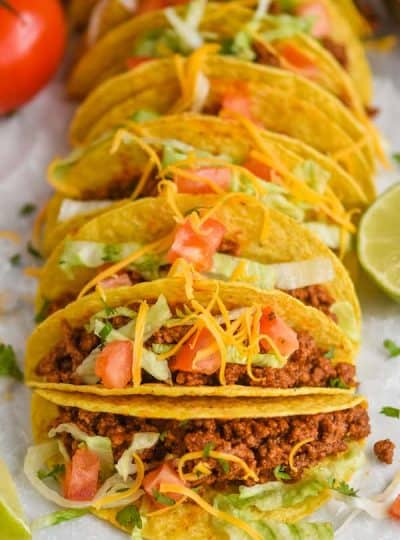 front view of a row of hard shell tacos with taco meet, and topped with tomatoes, lettuce, and cheese