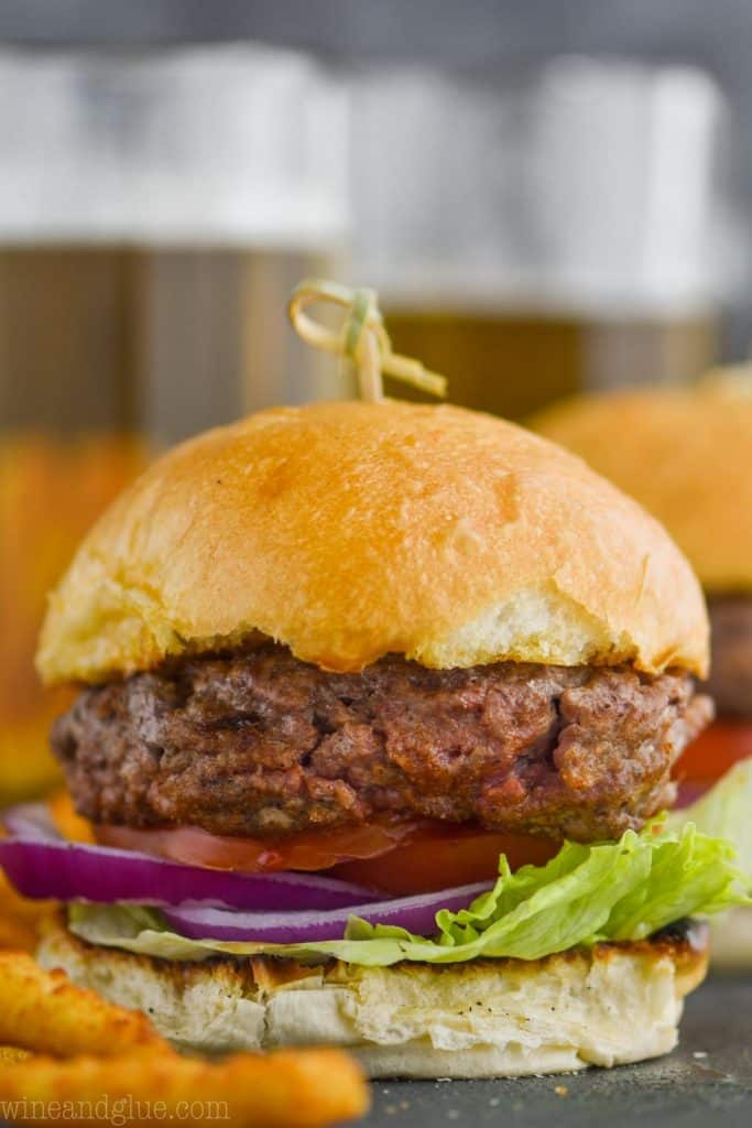 up close of a hamburger made with the best hamburger seasoning, garnished with red onion, tomatoes, and lettuce on a bun held by a toothpick