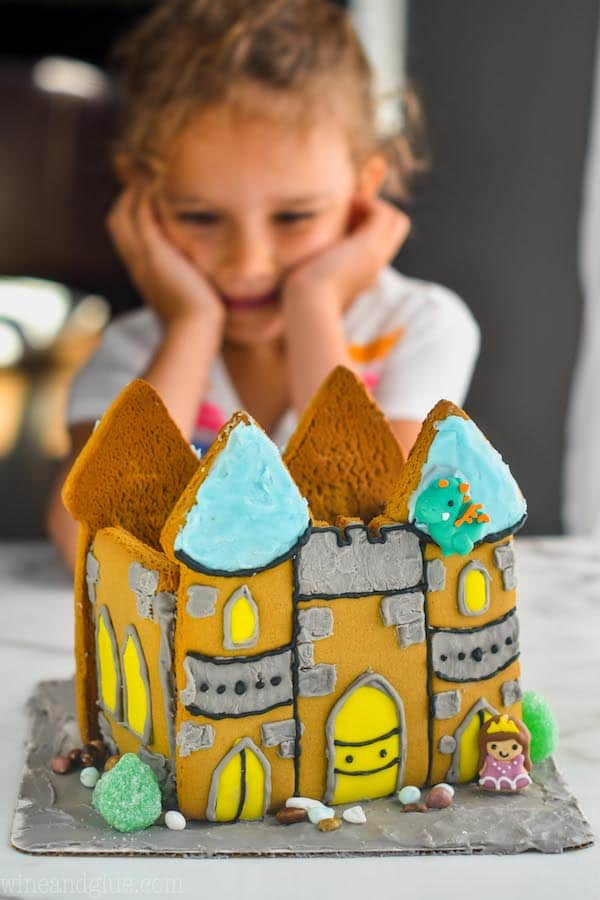 little girl in the background looking at a decorated gingerbread castle cookie creation