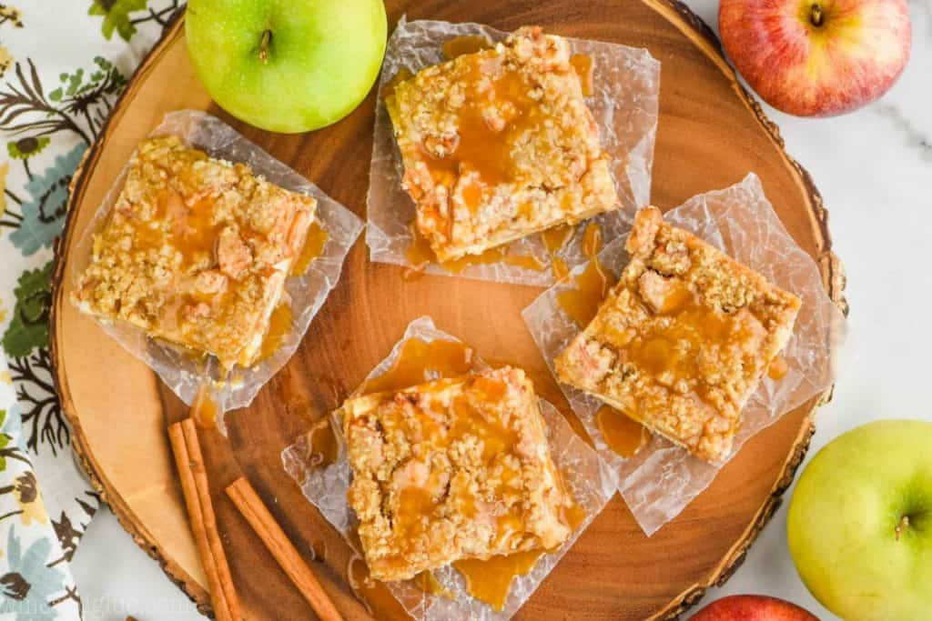 an overhead view of four apple cheesecake bars on wax paper on a circle wood platter