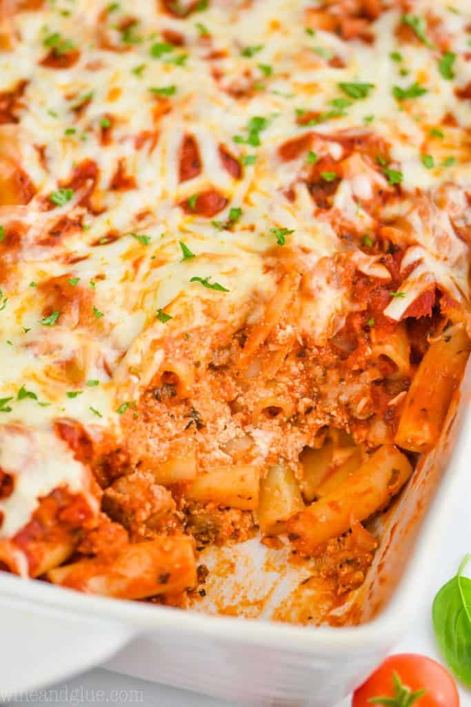 up close of a ceramic white dish of baked ziti that has been scooped into