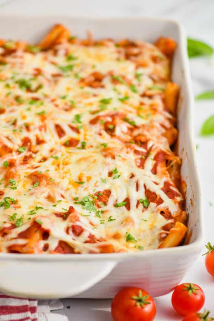 close up of a pan of baked ziti in a white ceramic dish, garnished with parsley