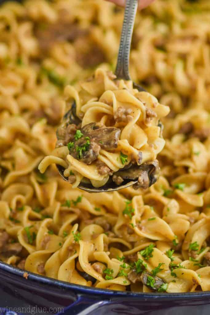serving spoon dishing up ground beef stroganoff recipe with egg noodles, sliced mushrooms, and fresh parsley