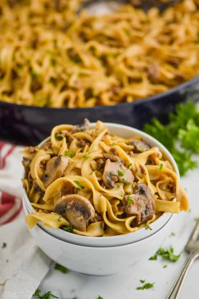 two stacked white bowls with the top one full of ground beef stroganoff recipe - egg noodles, mushrooms, parsley, and a skillet with the rest of the recipe in the background