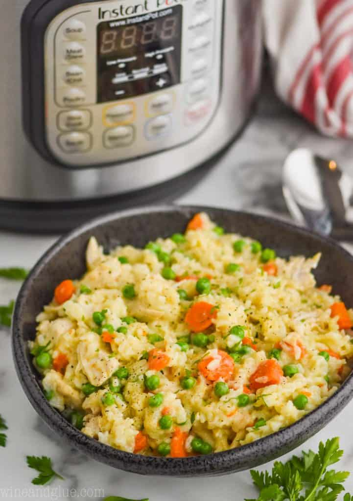 black bowl filled with instant pot chicken and rice casserole in front of an instant pot