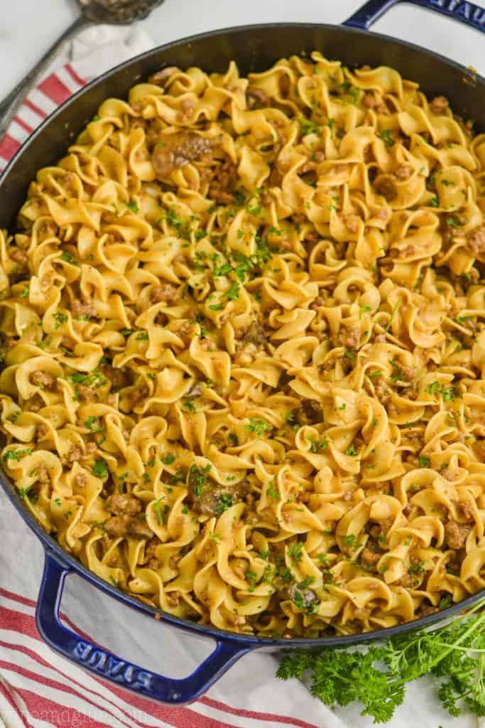 overhead view of ground beef stroganoff recipe in a large navy blue skillet on a white surface