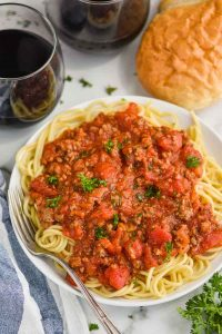overhead view of a white plate with spaghetti and homemade spaghetti meat sauce, two glass of red wine and french bread
