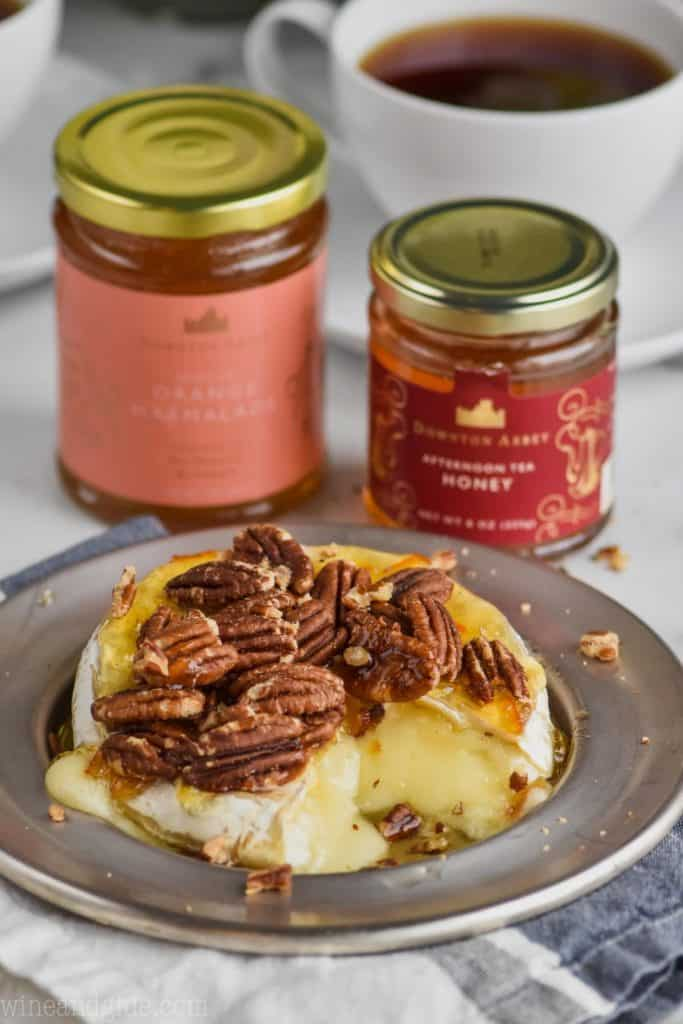 a silver plate with baked brie on it covered with honey, marmalade, pecans, and jars of honey and marmalade in the background