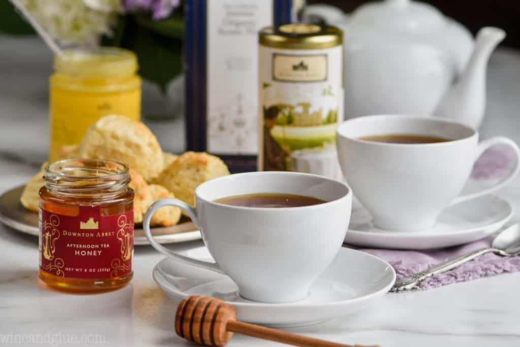a tea cup next to a jar of honey, with a honey stick in front, another tea cup in back, as well as a canister of tea, a scone mix, and flowers
