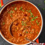 overhead view of a red stock pot with a vegetarian chili recipe and a metal ladle coming out of it