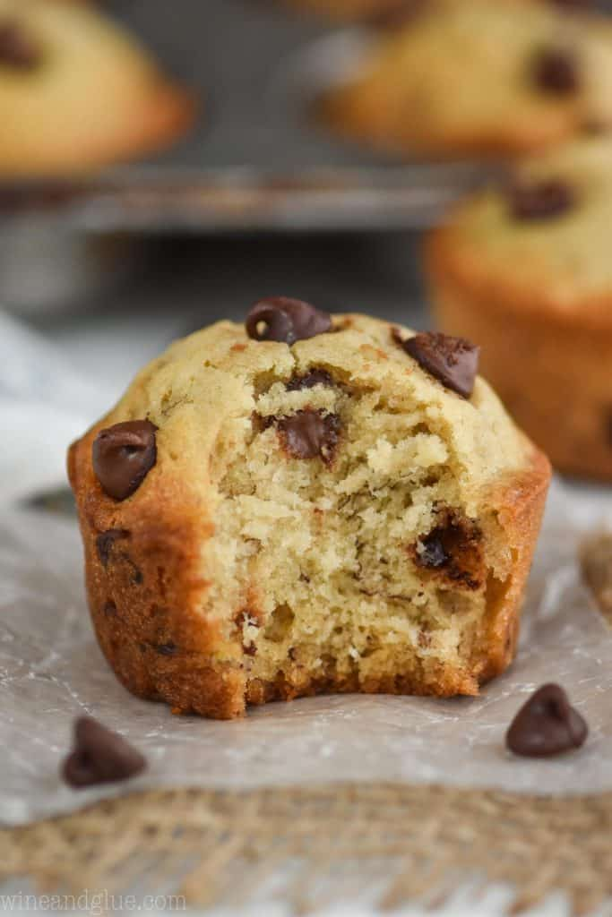 a close up of a banana chocolate chip muffin with a bite mixing