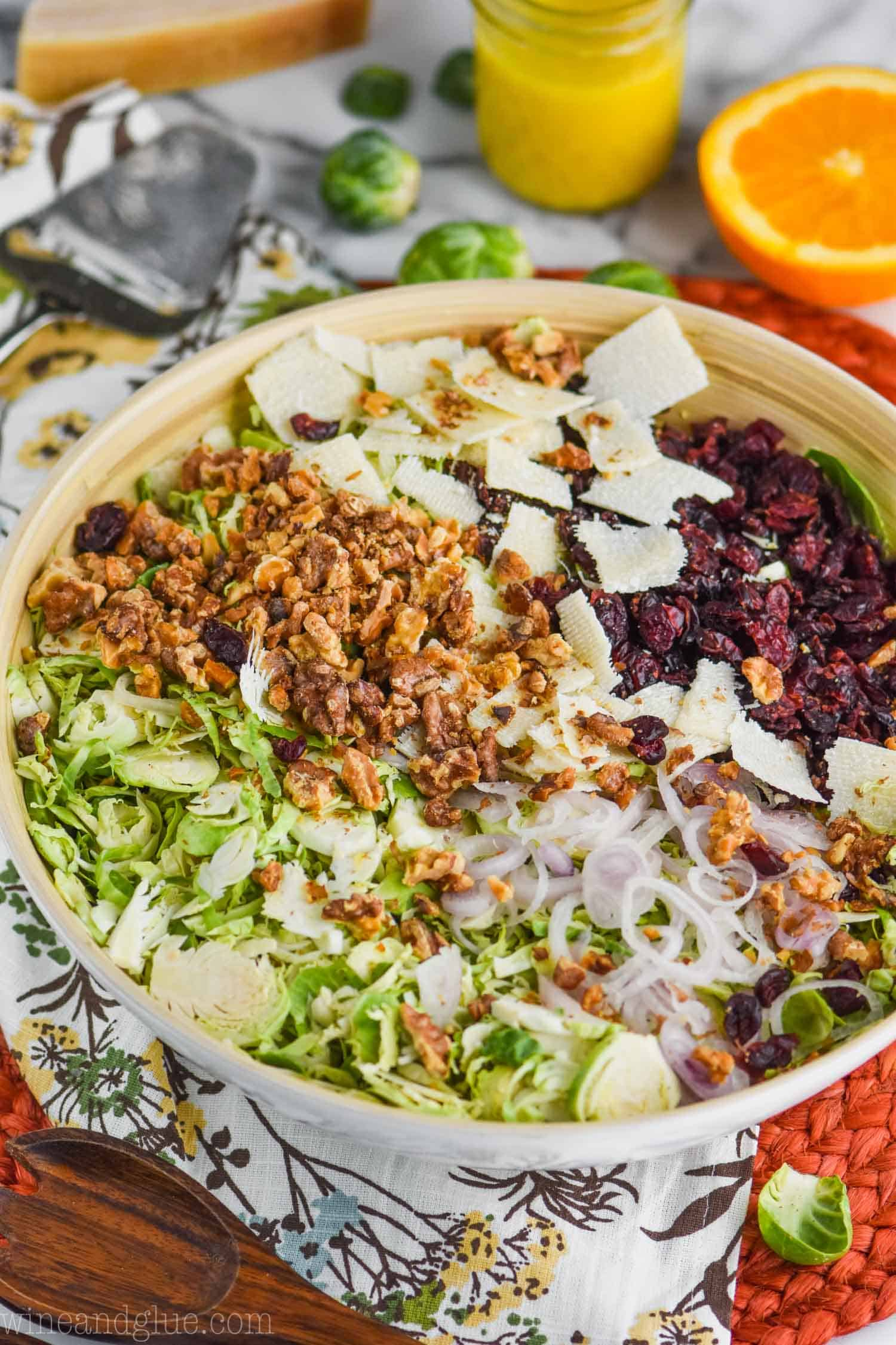 white wooden bowl with brussel sprouts salad with cranberries, shaved parmesan, walnuts and thinly sliced shallots