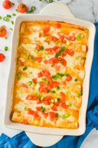 overhead view of white ceramic baking dish filled with buffalo chicken enchilada recipe that is garnished with green onions and chopped tomatoes