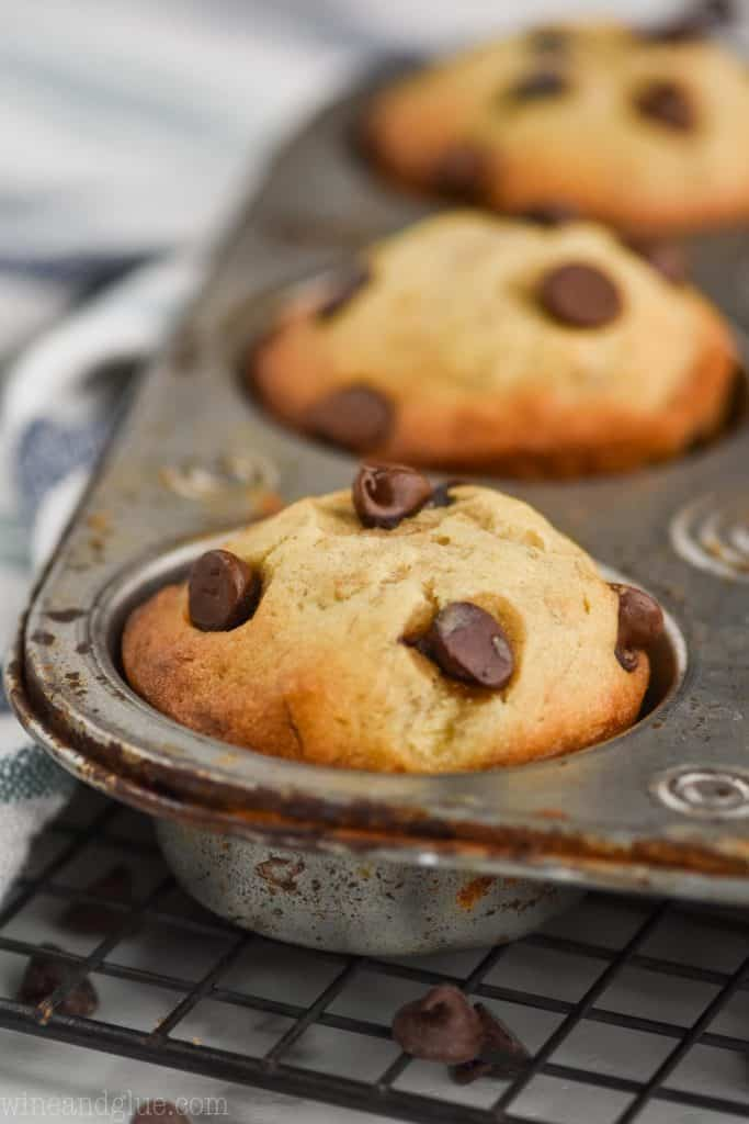 a close up of a banana chocolate chip muffin that is still in the muffin tin sitting on top of a wire cooling rack