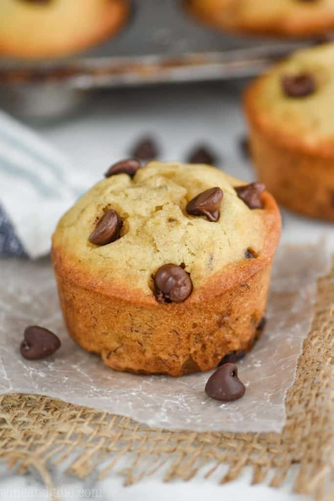 a single banana chocolate chip muffin sitting on wax paper with chocolate chips around it