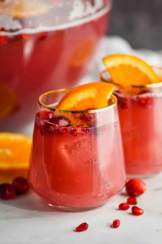 two glasses full of red holiday punch recipe with cranberries floating and orange slices in it