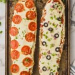 overhead view of two halves of a french bread pizza, one with pepperoni and the other with olives and peppers