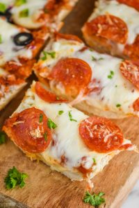 up close of a sliced piece of french bread pizza on a cutting board topped with pepperoni