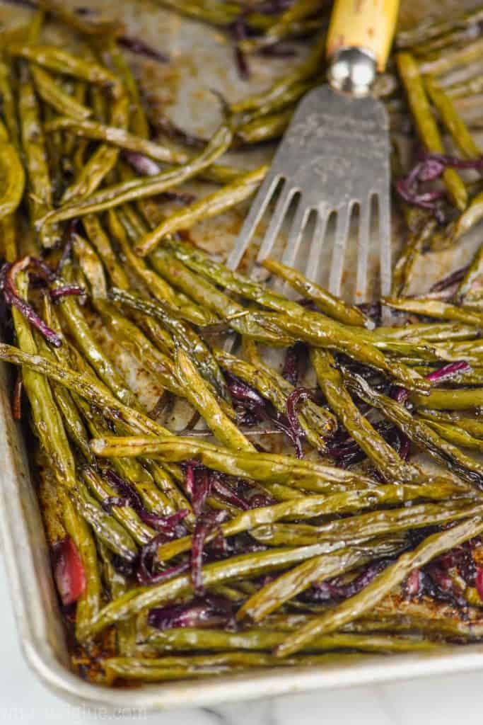 a wire spatula dishing up oven roasted green beans recipe