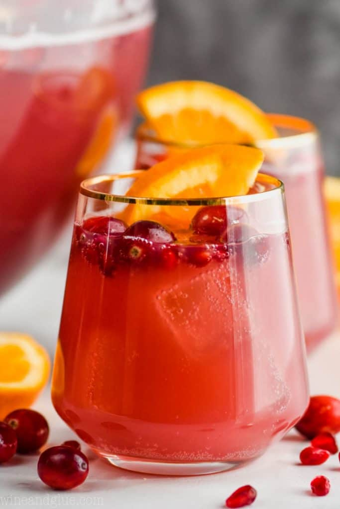 a gold rimmed wine glass full of non alcoholic holiday punch with cranberries floating in it and an orange wedge