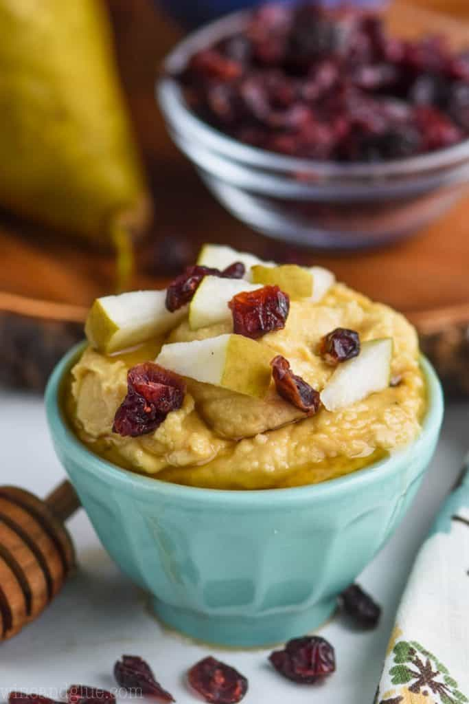 light teal bowl filled with hummus and topped with honey, pear pieces, and dried cranberries