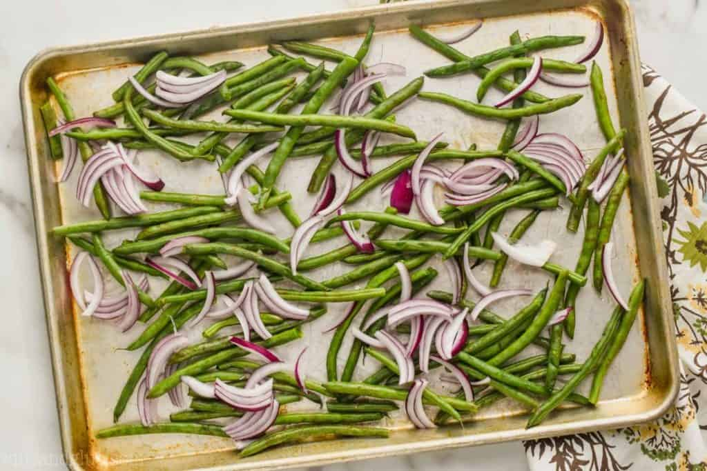 overhead view of rimmed baking sheet with green beans and sliced red onions to be oven roasted