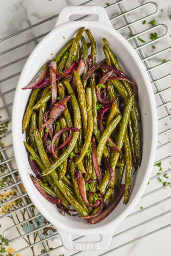 overhead view of a white roasting dish full of oven roasted green beans