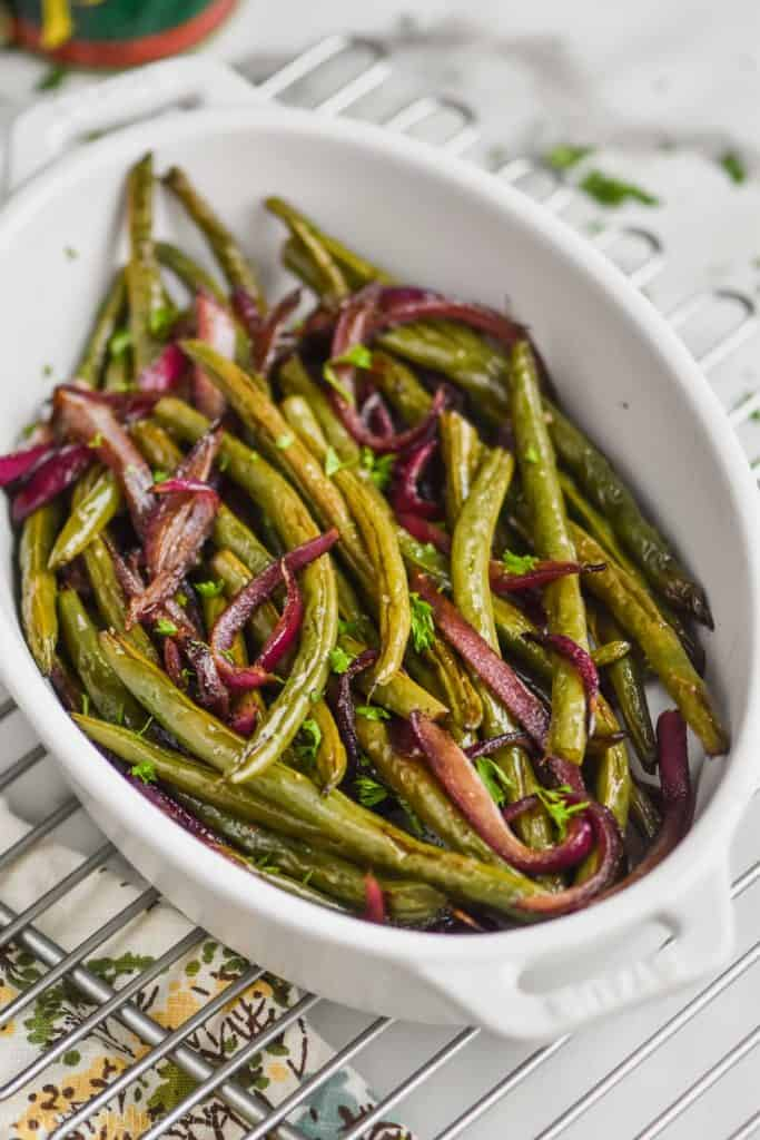 small white roasting dish full of roasted green beans on a wire rack