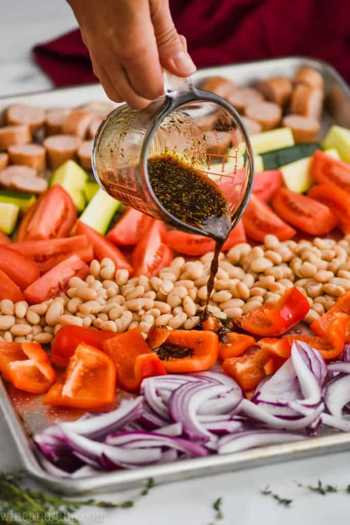 pouring a marinade over sheet pan dinner with beans, vegetables, and chicken sausages