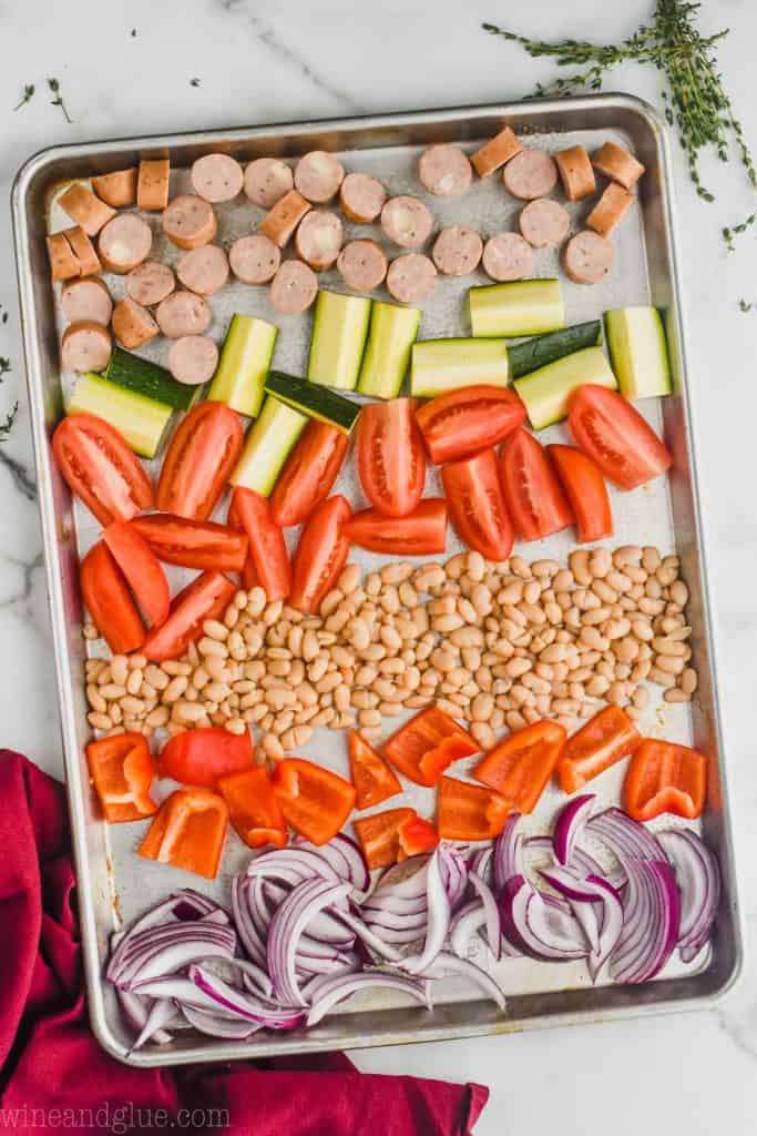overhead view of chicken sausages, zucchini, tomatoes, northern beans, red peppers, and red onions all chopped on a rimmed baking sheet to make sheet pan sausage and veggies