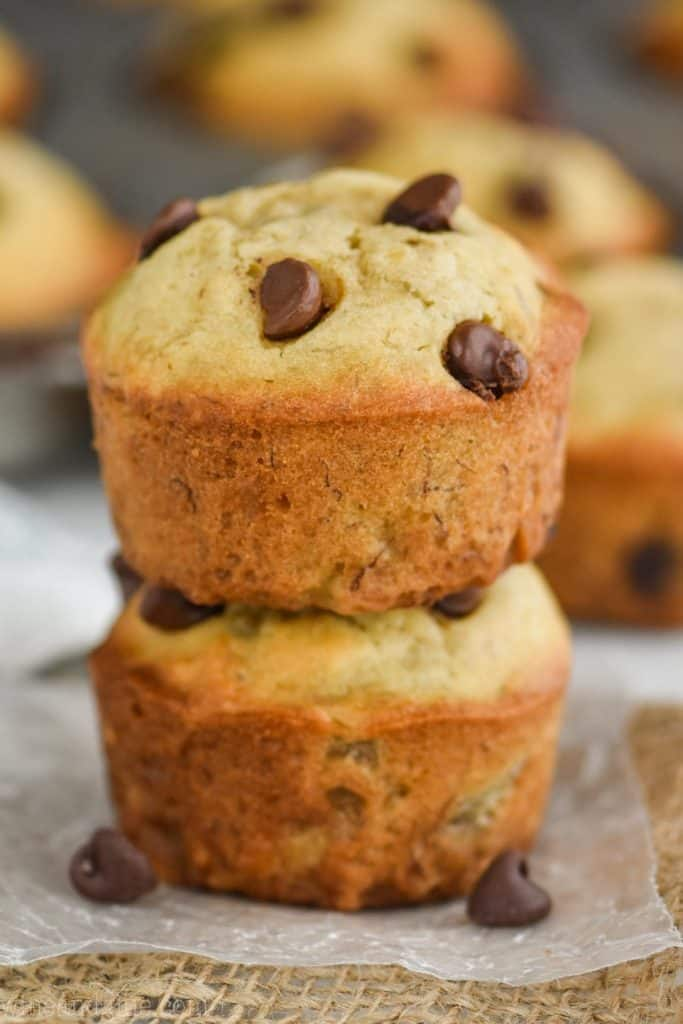 two banana chocolate chip muffins stacked on top of each other on top of wax paper with more muffins in the background