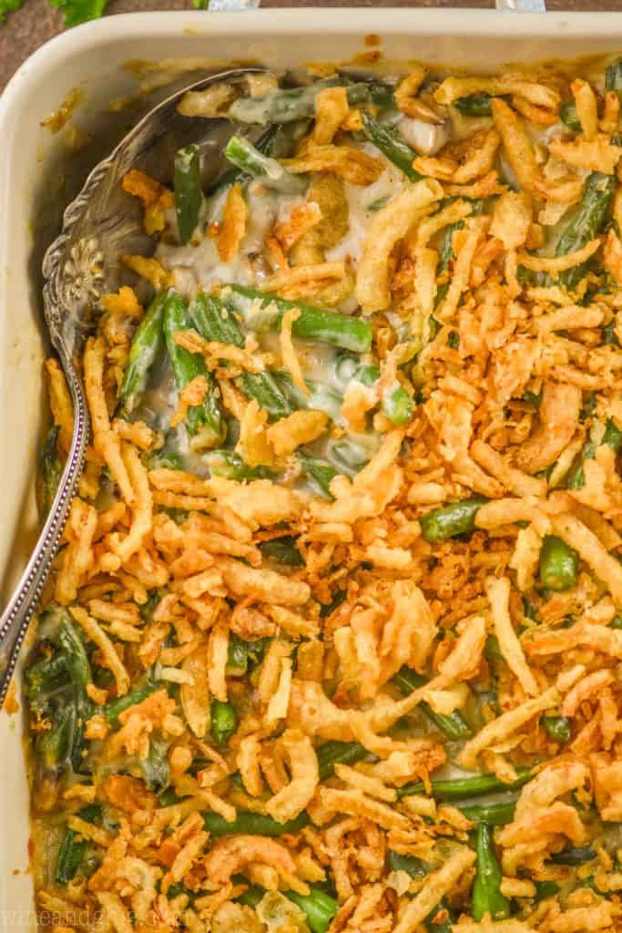 overhead close up of a green bean casserole being dished out of a baking dish