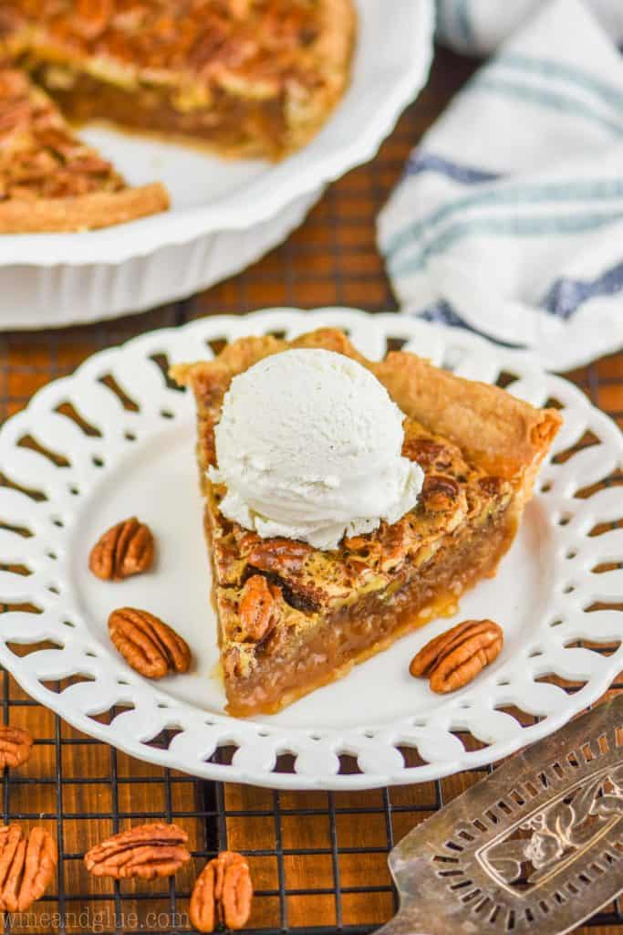 a piece of the best pecan pie on a fancy white plate with a large scoop of vanilla ice cream on top and the rest of the pie blurred in the background