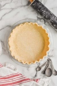 a pie crust recipe that has been transferred to a glass pie pan and the rim of it has been pinched
