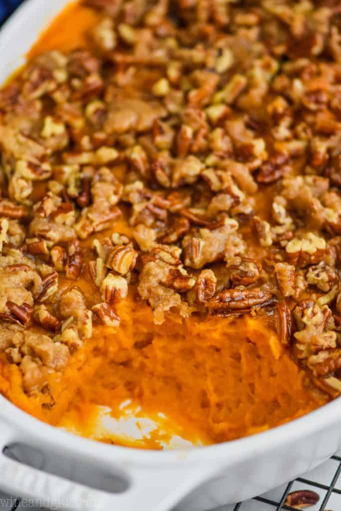 close close up of a sweet potato casserole that has been topped with pecans, butter, brown sugar, and flour and is in a white casserole dish where a scoop is missing