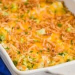white casserole dish filled with chicken broccoli and rice casserole topped with fried onions