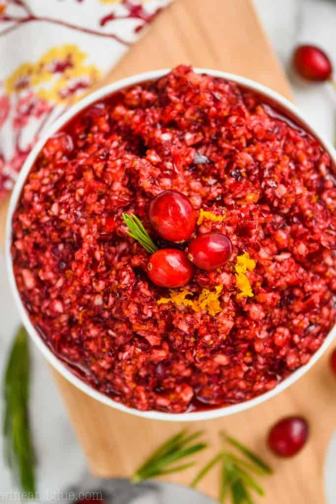 overhead view of cranberry orange relish that is in a white bowl and garnished with three cranberries, a little rosemary, and some orange zest