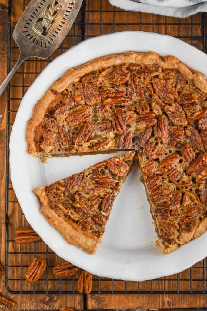overhead view of a pecan pie that has been cut into with a piece sitting waiting to be pulled out